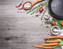 Fresh carrots from the garden with herbs and spices with a vintage cast-iron frying pan wooden rustic background top view borde Stock Image