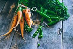 Fresh carrots with green tops and pods of peas Royalty Free Stock Photography