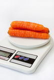 Fresh carrots on a kitchen digital scale Royalty Free Stock Photography