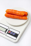 Fresh carrots on a kitchen digital scale Royalty Free Stock Photo