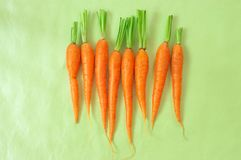Fresh carrots on light green background. Pile of fresh carrots on light green background. Top view point Stock Photography