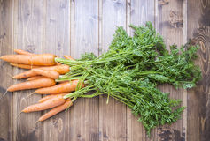 Fresh carrots over  wooden table from ecological farming. Some fresh carrots over  wooden table from ecological farming. Closeup Stock Images