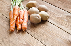 Fresh carrots  and potatoes on a  wooden background. Fresh carrots and potatoes on a light wooden background Royalty Free Stock Photography