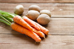 Fresh carrots  and potatoes on a  wooden background. Fresh carrots and potatoes on a light wooden background Royalty Free Stock Photo