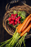 Fresh carrots and radish in the basket. Stock Photo