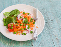 Fresh carrots, radishes, spinach and green peas salad. Healthy food. Royalty Free Stock Photos