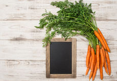 Fresh carrots roots with green leaves blackboard Royalty Free Stock Images