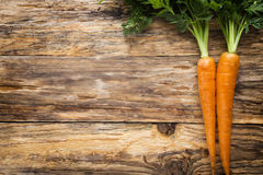 Fresh carrots on the wooden background. Royalty Free Stock Photos