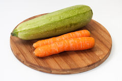 Fresh carrots and zucchini on a kitchen wooden board Stock Image