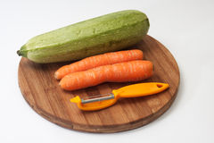Fresh carrots and zucchini on a kitchen wooden board with a knif Stock Photo