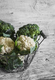 Fresh cauliflower and broccoli in a vintage metal basket. On a light wooden surface Royalty Free Stock Photography