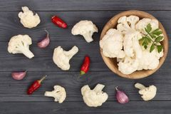 Fresh cauliflower cut into small pieces in wooden bowl with garlic and chili peppers on black background Royalty Free Stock Image