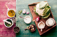 Fresh cauliflower with savory ingredients. For a gourmet vegetarian dish standing ready to prepare the meal on a colorful shabby chic wooden background Royalty Free Stock Photography