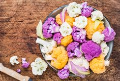 Fresh cauliflowers on rustic wood. Fresh cauliflowers top view in bowl on rustic dark wood  background Stock Image