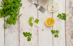 Fresh Celery. With onion lemon and a fork on white wooden background Royalty Free Stock Photo