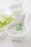 Fresh celery sticks with yogurt dip on white wooden background Stock Photography