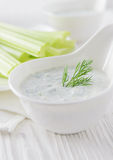 Fresh celery sticks with yogurt dip on white wooden background Stock Photo