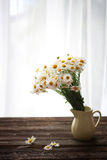 Fresh chamomile flowers on the wooden table. Bouquet of wildflowers on a rustic table at country cottage Stock Photography