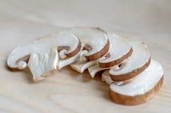 Fresh champignon mushrooms. Fresh sliced champignon mushrooms on wooden chopping board Stock Photo