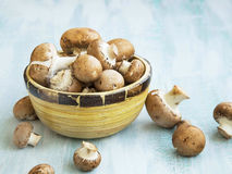 Fresh champignon mushrooms in a wooden bowl Stock Photo