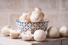 Fresh champignons on a cutting board and in a bowl Royalty Free Stock Images