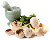 Fresh champignons, garlic and basil in wooden bowls near a morta Royalty Free Stock Images