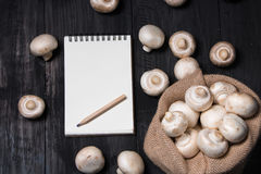 Fresh champignons and note for record on black table.  royalty free stock photos
