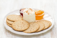 Fresh cheese with cookies and jam on white dish Stock Photography