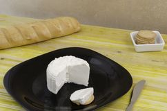 Fresh cheese over black dish and wood. Stock Photos