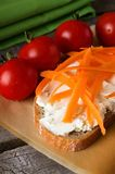 Fresh cheese on slice of bread with carrot shaves Stock Photos