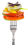 Fresh cheese with vegetables on fork Stock Images