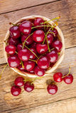 Fresh cherries in basket on wood Royalty Free Stock Images