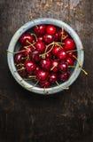 Fresh cherries berries in blue bowl on dark rustic wooden background Stock Photo