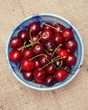 Fresh cherries berries in blue bowl. On sackcloth background Royalty Free Stock Photos