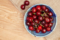 Fresh cherries berries in blue bowl. On sackcloth and wooden background Royalty Free Stock Photography