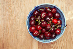 Fresh cherries berries in blue bowl. On wooden background Stock Photo