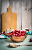Fresh cherries berries in old pan on rustic kitchen background Stock Photos