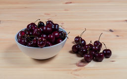 Fresh cherries berries in white bowl on  wooden background. Royalty Free Stock Photo