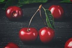 Fresh cherries on black wooden background Stock Images
