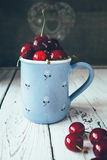 Fresh cherries are in blue mug Stock Image