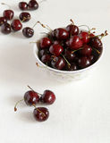 Fresh cherries in bowl and kitchen napkin. White cloth from flax. Healthy food concept Royalty Free Stock Image