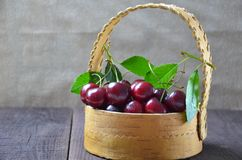 Fresh cherries in bowl on table. A child boy is picking up some cherries with his left hand from a bsket, closeup stock image