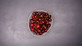 Fresh cherries in bowl on table stop motion stock video