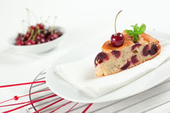 Fresh Cherries Cake. A slice of fresh cherries cake with a fresh cherry on top and a bud of mint. Shallow depth of field on the cherry and the cake's tip Royalty Free Stock Photo