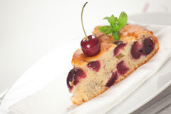 Fresh Cherries Cake. A slice of fresh cherries cake with a fresh cherry on top and a bud of mint. Shallow depth of field on the cherry and the cake's tip Stock Images
