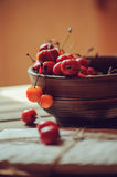 Fresh cherries close up in clay handmade plate on wooden table Royalty Free Stock Photos