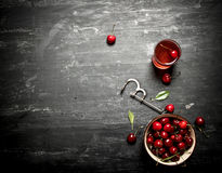 Fresh cherries in the Cup and juice in the glass. Fresh cherry in the Cup and juice in the glass. On a black wooden background Royalty Free Stock Photos