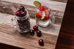 Fresh cherries and cup of water with fruit on wooden table. Fresh cherries and cup of water with fruit, cucumber, strawberry on wooden table Stock Photos