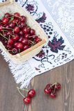Fresh cherries on embroidered towel. Fresh cherries in basket on embroidered towel royalty free stock photography