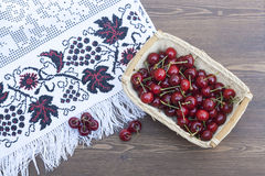 Fresh cherries on embroidered towel. Fresh cherries in basket on embroidered towel royalty free stock images